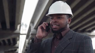 Smiling professional man in blank white hard hat on phone while standing under highway bridges