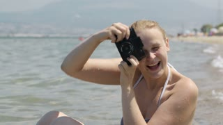 Smiling woman in a bikini sitting on the beach at the edge of the water taking a photograph at the seaside with her vintage camera with plastic lens