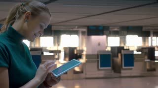 Smiling woman is writing something in tablet while standing by check-in gates in the airport.
