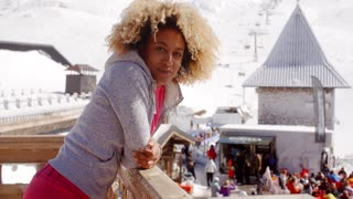 Smiling woman leaning on railing at ski resort