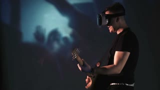 Smiling young man playing guitar while wearing oculus rift goggles