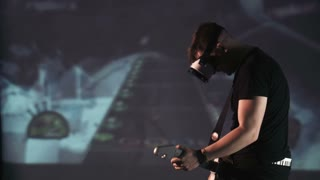Smiling young man playing in virtual 360 degree guitar game while wearing oculus rift VR goggles