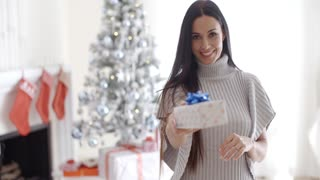 Smiling young woman holding out a Christmas gift