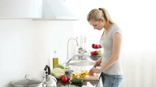 Smiling young woman in kitchen cutting bell peppers on cutting board for salad