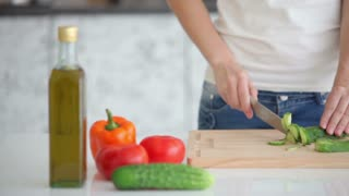 Smiling young woman in kitchen cutting vegetables and looking at camera