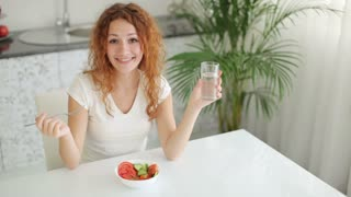 Smiling young woman sitting at kitchen table holding glass of water and eating vegetable salad
