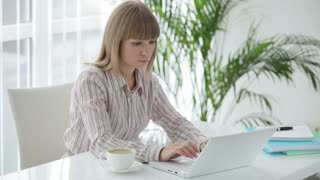 Smiling young woman sitting at office table with cup of coffee and working on laptop