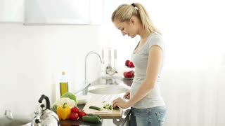 Smiling young woman standing at kitchen table cutting cucumbers on cutting board and looking at camera