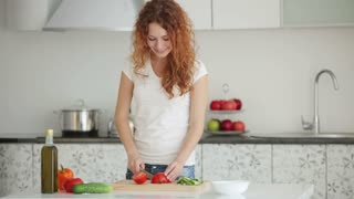 Smiling young woman standing in kitchen slicing tomatoes