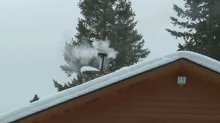 Smoky Chimney On Snowy Roof
