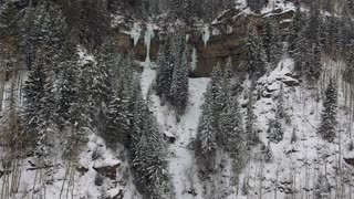 Smooth slow flight over snow covered trees to ice waterfall in the Rocky Mountains