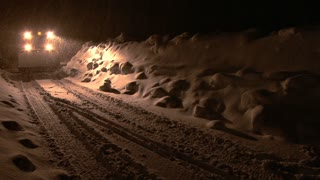 Snow Plow Moves Down Road at Night During Snowstorm
