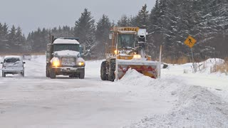 Snowblower Blowing Snow into Dump Truck to Clear Road