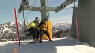 Snowboarder And Small Child Get Off Chairlift