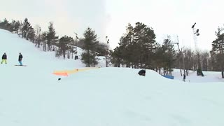 Snowboarder does a 360 off jump