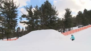 Snowboarder does a 900 degree rotation off jump