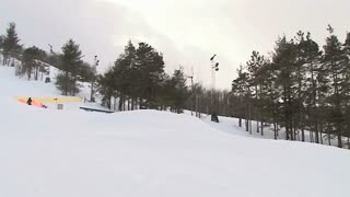 Snowboarder does a nose grab off jump