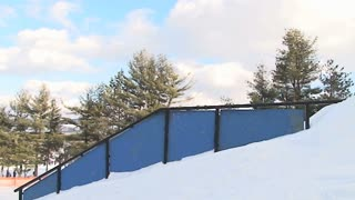 Snowboarder jumps onto rail