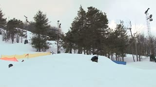 Snowboarder soars through the sky off jump