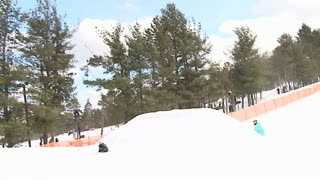 Snowboarder throws a 720 grab off jump