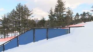 Snowboarder zips across rail