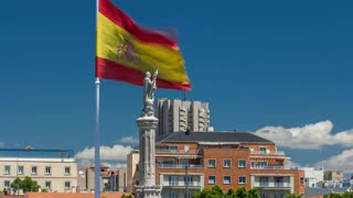 Spanish flag waves behind statue of Christopher Columbus timelapse with clouds on blue sky, plaza de Colon in Madrid, Spain 4K
