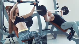 Sportsman and sportswoman doing inclined bench press in gym