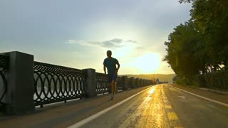 Sportsman in blue clothes running on summer sunset embankment in Moscow. Super slow motion steadicam shot at 240 fps