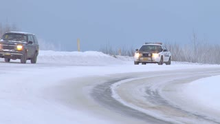 State Trooper Passes Winter Traffic on Snowy Mountain Road