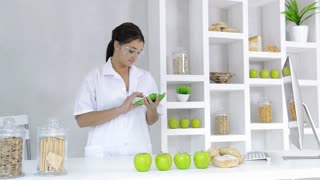 brunette nutrition technician receiving message on mobile phone while working