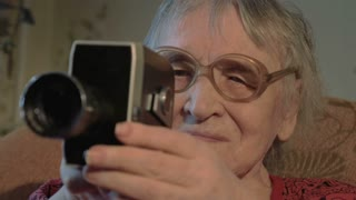 Steadicam and close-up shot of a senior woman in glasses using retro camera while sitting in the arm-chair at home