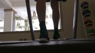 Steadicam low angle shot of a male feet walking on treadmill with following view through the window on hotel restaurant