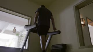 Steadicam low angle shot of a mature man exercising on treadmill working on low speed. Gym in the hotel with view on the terrace
