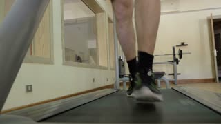 Steadicam low angle shot of male feet running on stepmill. Gym in the hotel with view to the hall
