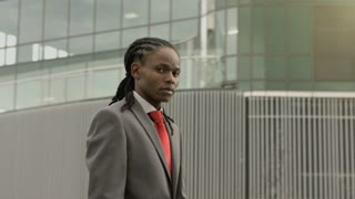 Steadicam portrait shot of African American business man in modern glass city.