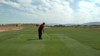 Steadicam Shot As Man Tees On Golf Course With Red Rock Cliffs And Distance