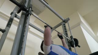 Steadicam shot of a strong young man working out hard doing chest press. Healthy life with sport