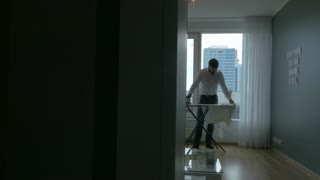 Steadicam shot of a youg man ironing the clothes at home. He standing by the big window with city panorama