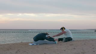 Steadicam shot of a young couple sitting on the beach. They doing stretching exercises while listening to music in wireless headphones