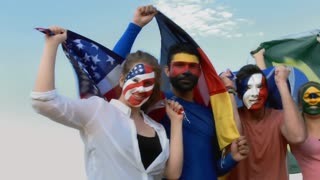 Steadicam shot of a young group of patriotic supporters celebrating with their country flag and face painting.