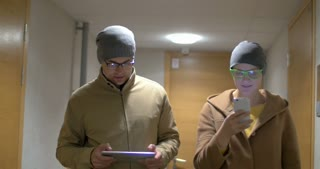 Steadicam shot of a young hipster style man and woman walking along the hotel corridor and talking while using tablet computer and smart phone