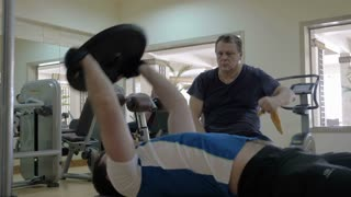 Steadicam shot of a young man lying on the bench in the gym and doing exercise with weight plate, putting it up and down. Another man looking at him while having a break