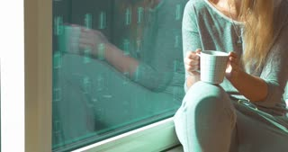 Steadicam shot of a young woman sitting on the windowsill with a cup of tea. She';s drinking the beverage and looking out the window.