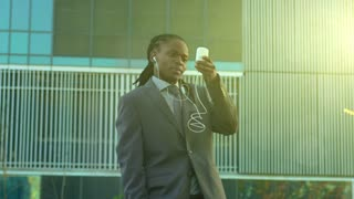steadicam shot of African American business man on his mobile phone at sunrise in modern city.