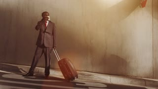 Steadicam shot of African American business man with laptop bag, his early morning coffee as he is commuting to work or airport in a modern city street at sunrise.