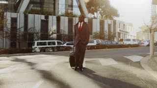Steadicam shot of African American business man with laptop bag on while commuting to work or airport as he walks in a modern city street at sunrise.