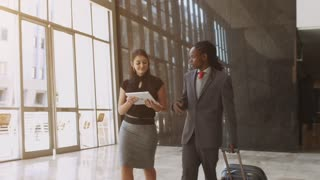 Steadicam Shot of African American man meeting business associate in modern glass office building.