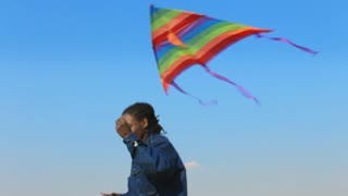 Steadicam shot of African American man running and flying kite.