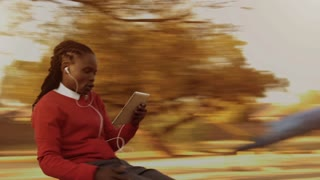 Steadicam shot of African American man spinning while using a tablet computer for video calling in park at sunrise