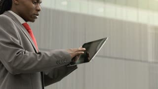 Steadicam shot of African American man using touch screen tablet computer at sunrise in city .